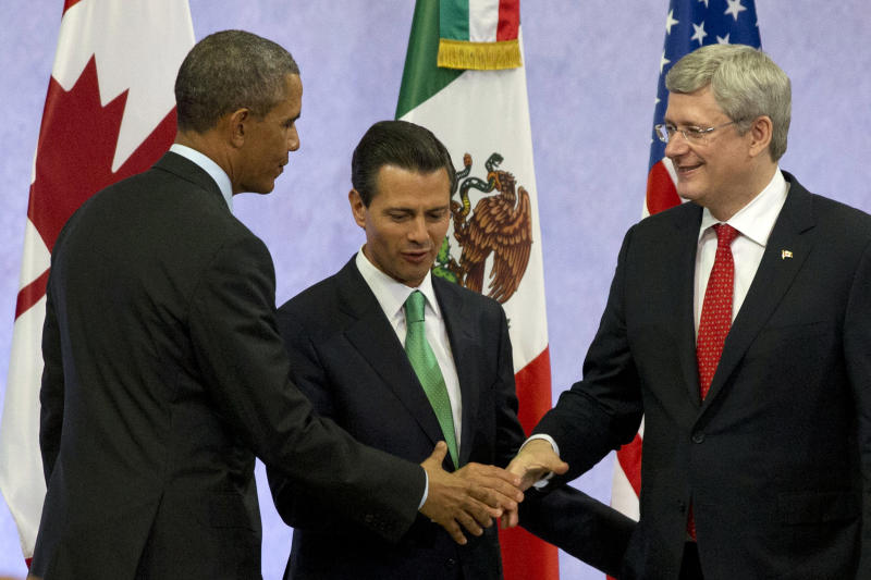 "U.S. President Barack Obama, left, Mexican President Enrique Peña Nieto, and Canadian Prime Minister Stephen Harper shake hands at the end of a news conference after the seventh trilateral North American Leaders Summit Meeting in Toluca, Mexico, Wednesday Feb. 19, 2014. This year's theme is ""North American Competitiveness."" (AP Photo/Jacquelyn Martin)"