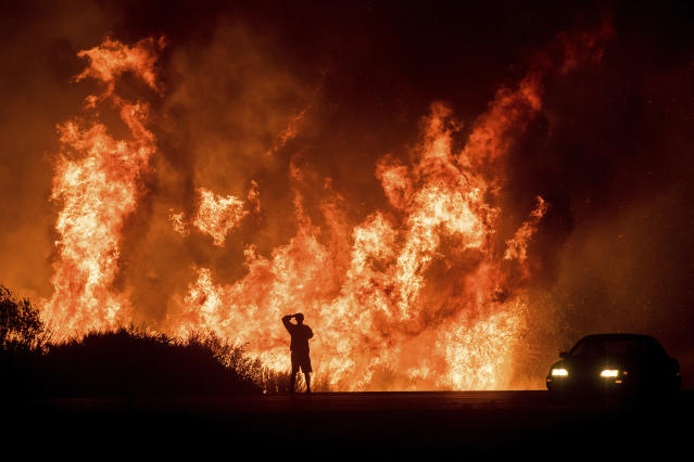 <p>A motorists on Highway 101 watches flames from the Thomas fire leap above the roadway north of Ventura, Calif., on Wednesday, Dec. 6, 2017. (Photo: Noah Berger/AP) </p>