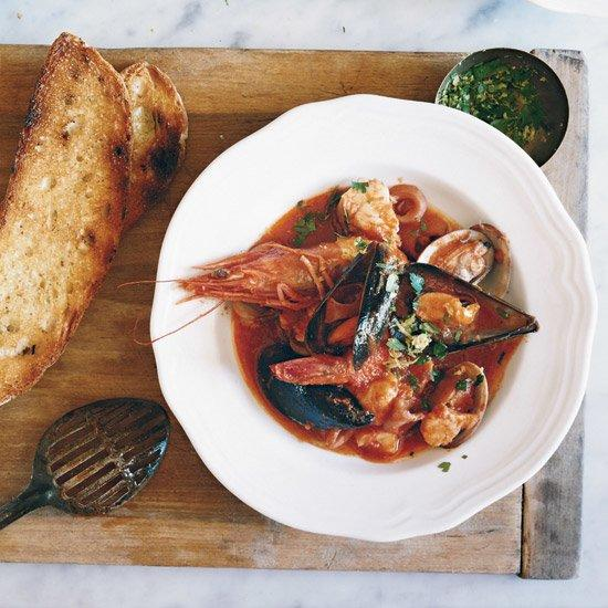 "<p>In this luscious, tomato-rich stew, Marco Canora cooks calamari slowly until it becomes supertender. He says calamari is absolutely essential to the success of the dish, because it releases its liquid as it simmers, which adds a huge amount of flavor to the sauce. ""I'm a big fan of substitutions,"" he says, ""but not in this case.""</p><p><a href=""https://www.foodandwine.com/recipes/italian-seafood-stew"">GO TO RECIPE</a></p>"