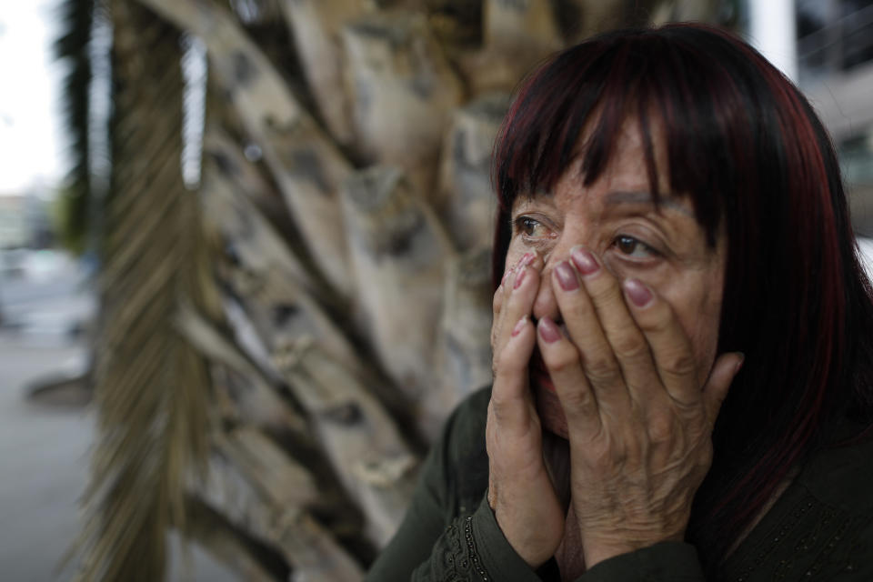 """Sex worker Laura cries as she talks about having to pawn her cell phone the day before in order to eat, after running out of money to pay for her rented room at the end of February, as she waits for clients outside the Revolution subway station, in Mexico City, Sunday, March 14, 2021. After more than 45 years as a street sex worker, Laura, 62, says she has known a new level of poverty since the pandemic began. """"I have lived many beautiful times, and now sad ones. But I'm still living."""" (AP Photo/Rebecca Blackwell)"""