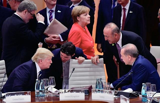 <p>President Donald Trump (L) talks to the President of Turkey Recep Tayyip Erdogan (R) while German Chancellor Angela Merkel is seen in the background before the beginning of first working session of the G20 Nations Summit with the topic 'Global Growth and Trade' on July 7, 2017 in Hamburg, Germany. (Photo: Thomas Lohnes/Getty Images) </p>