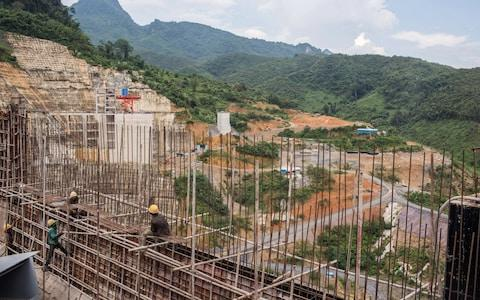 Workers prepare reinforcing steel at the Nam Tha 1 hydroelectric dam construction site - Credit: Bloomberg/Taylor Weidman