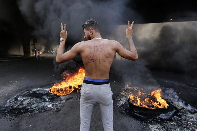 An anti-government protester with Arabic on his back