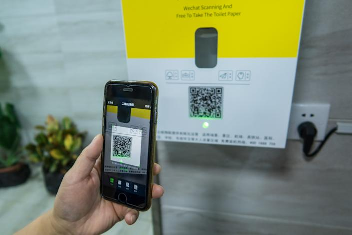 A citizen uses WeChat to scan a QR code to obtain toilet paper at a public restroom.