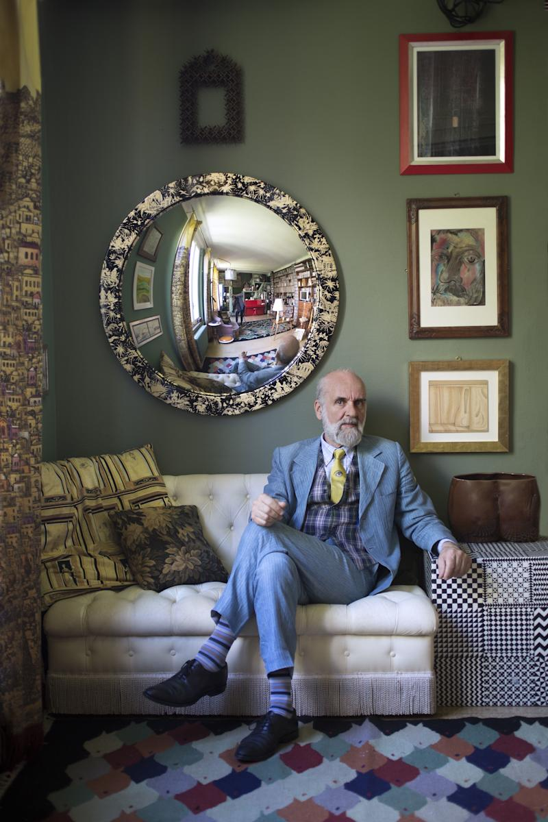 """Barnaba Fornasetti in his music room at home in Milan. The design of each of Casa Fornasetti's rooms invites you to consider decor in new ways, taking you inside an alternate reality, or as Barnaba says, a 'surreality'. The many convex mirrors for example, offer guests a distorted view of themselves, porcelain cats are curled up on desks and beds, and ceramic or fabric butterflies dance across lamps, tables and floors. Barnaba prefers not to leave the house for any great length of time: """"I am absolutely addicted to it. My home is a protective oasis in perpetual transformation. It represents my life: my job, my interests and my philosophy—all entwined."""""""