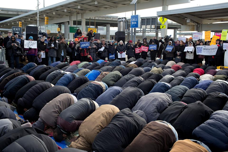 Supporters stand in the background as Muslims participate in a prayer in the parking lot of Terminal 4 at JFK International Airport on February 3, 2017.