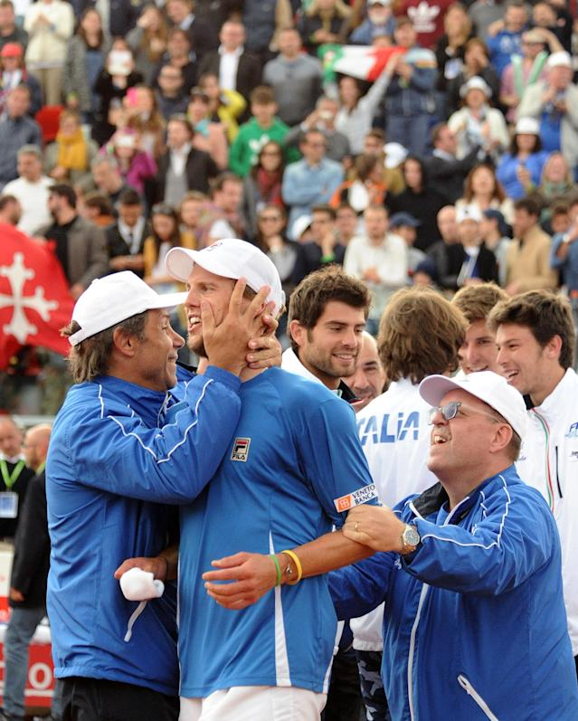 Italy's Andreas Seppi celebrates with team members after beating Britain's James Ward during a Davis Cup World Group quarterfinal tennis match in Naples, Italy, Sunday, April 6, 2014. Italy won both singles matches against Britain in straight sets on Sunday to reach the Davis Cup semifinals for the first time in 16 years. Fabio Fognini pulled off a surprise 6-3, 6-3, 6-4 victory over two-time Grand Slam champion Andy Murray to level the best-of-5 quarterfinal at 2-2 before Andreas Seppi defeated James Ward 6-4, 6-3, 6-4 in the decisive match. (AP Photo/Salvatore Laporta)