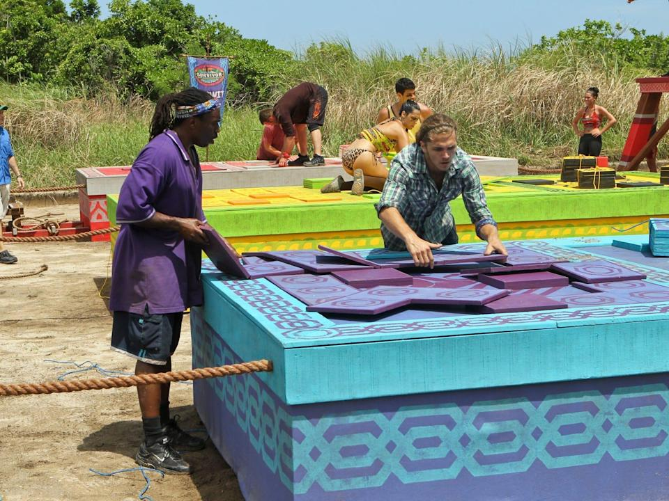 Russell Swan and Malcolm Freberg solving a purple and blue puzzle on survivor