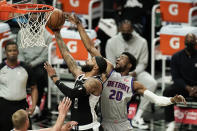 Los Angeles Clippers' Marcus Morris Sr., left, shoots under defense by Detroit Pistons' Josh Jackson during the first half of an NBA basketball game Sunday, April 11, 2021, in Los Angeles. (AP Photo/Jae C. Hong)