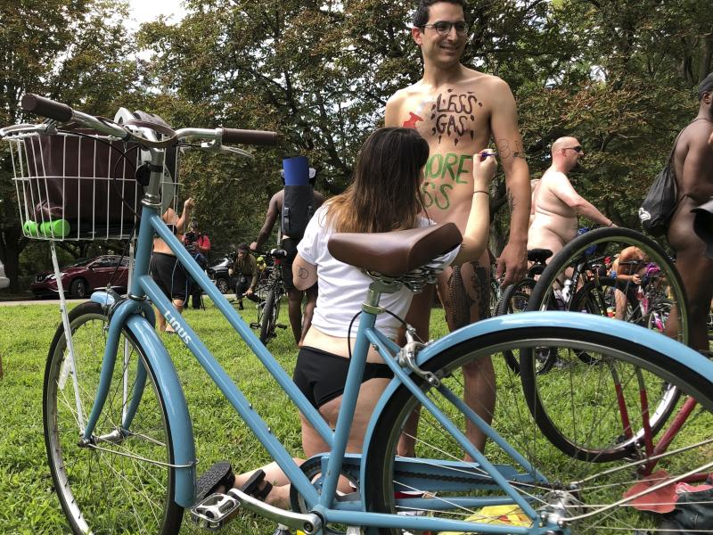 Nude bicyclist Oren Roth-Eisenberg has a message opposing fossil fuel consumption painted on his torso by his wife before the start of the Philly Naked Bike Ride in Philadelphia on Saturday, Aug. 24, 2019. (AP Photo/Dino Hazell)
