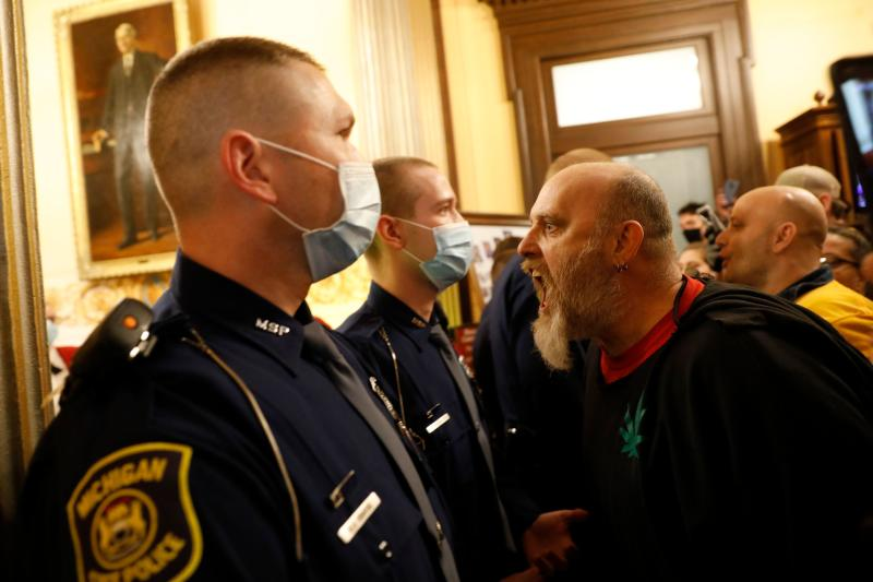 Protestors try to enter the Michigan House of Representative chamber and are being kept out by the Michigan State Police after the American Patriot Rally organized by Michigan United for Liberty protest for the reopening of businesses on the steps of the Michigan State Capitol in Lansing, Michigan on April 30, 2020.(Photo by JEFF KOWALSKY/AFP via Getty Images)