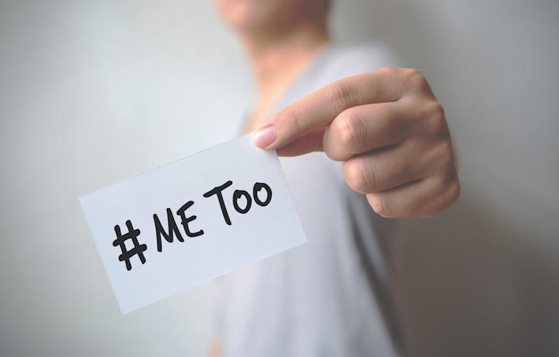 "Close up hand of young man holding show a white card with word ""Me Too"". Social movement concept"