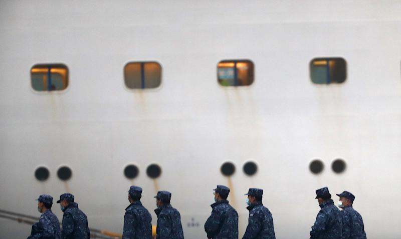 Japan Self-Defense Forces walk past the Diamond Princess cruise ship, with people quarantined onboard due to fears of the new coronavirus, at the Daikaku Pier Cruise Terminal in Yokohama port on Feb. 16, 2020. The number of people who have tested positive for the new coronavirus on a quarantined ship off Japan's coast has risen to 355, the country's health minister said.