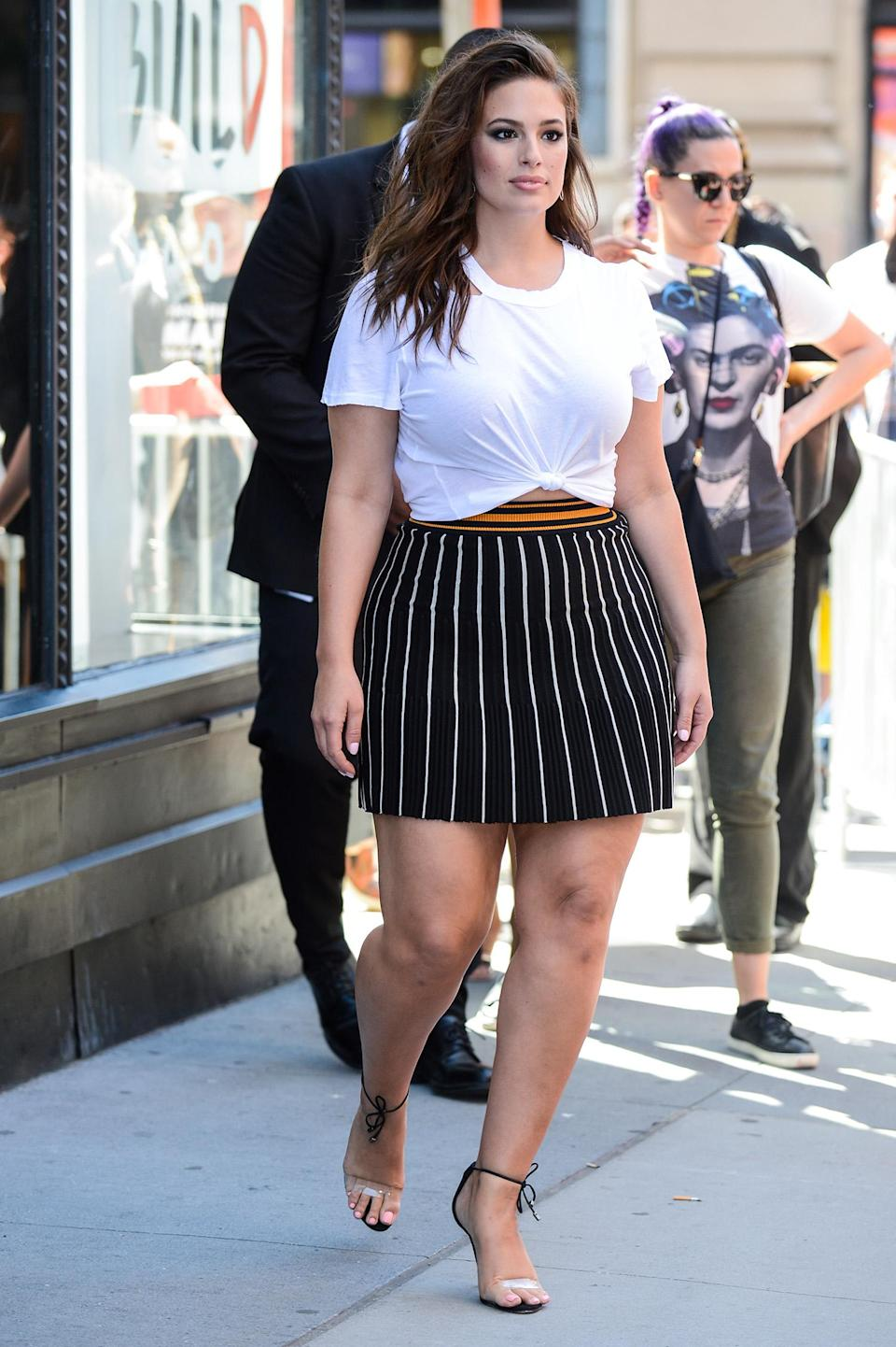 <p>The model wears the n:Philanthropy Harlow Distressed BFF Tee in white with a pinstriped black-and-white miniskirt. (Photo: Getty Images) </p>