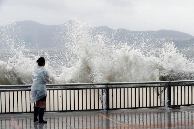 <p>A woman stands beside a big wave on a waterfront Typhoon Hato hitting in Hong Kong, China, Aug. 23, 2017. (Photo: Tyrone Siu/Reuters) </p>