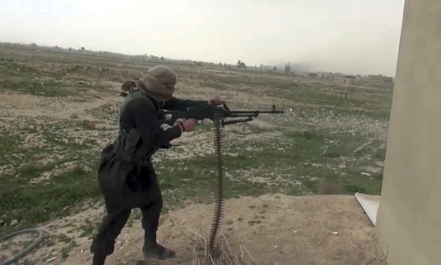 FILE - This a file frame grab from video posted online Friday, Jan. 18, 2019, by supporters of the Islamic State group, purports to show an IS fighter firing a weapon during clashes with members of the U.S.-backed Syrian Democratic Forces, in the eastern Syrian province of Deir el-Zour, Syria. (Militant Photo via AP, File)