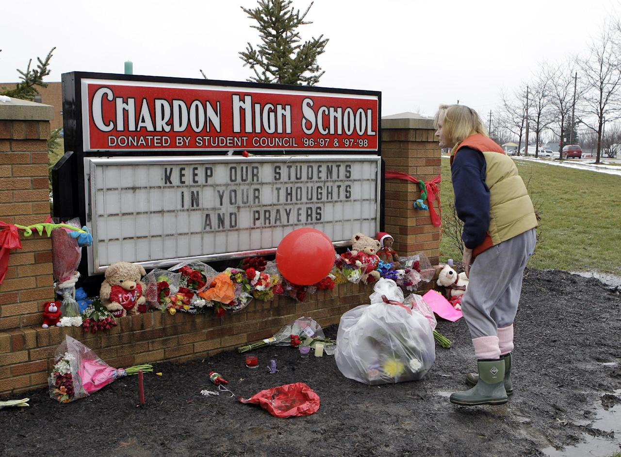 Helga Davies pauses after placing a basket of flowers at a memorial in front of Chardon High School in Chardon, Ohio Wednesday, Feb. 29. The Geauga County town 30 miles east of Cleveland is mourning the death of three students and the wounding of two others in a shooting at the high school Monday morning. (AP Photo/Mark Duncan)