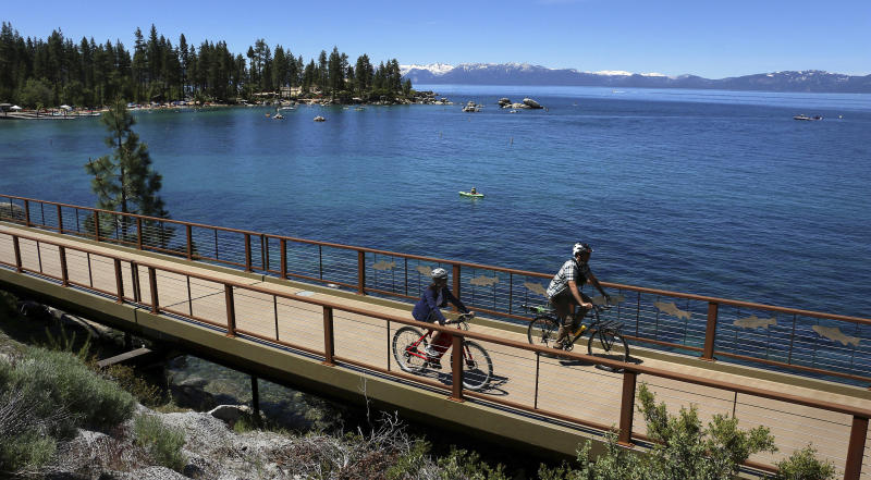 FILE - This June 25, 2019 file photo shows cyclists on the Tahoe East Shore Trail near Glenbrook, Nev. Water stored at Lake Tahoe has nearly reached its legal limit after snowmelt from a stormy winter left behind enough to potentially last through up to three summers of drought. The lake has been within an inch of its maximum allowed surface elevation of 6,229.1 feet above sea level for more than three weeks and crept to within a half-inch this week. (Jason Bean/The Reno Gazette-Journal via AP, File)