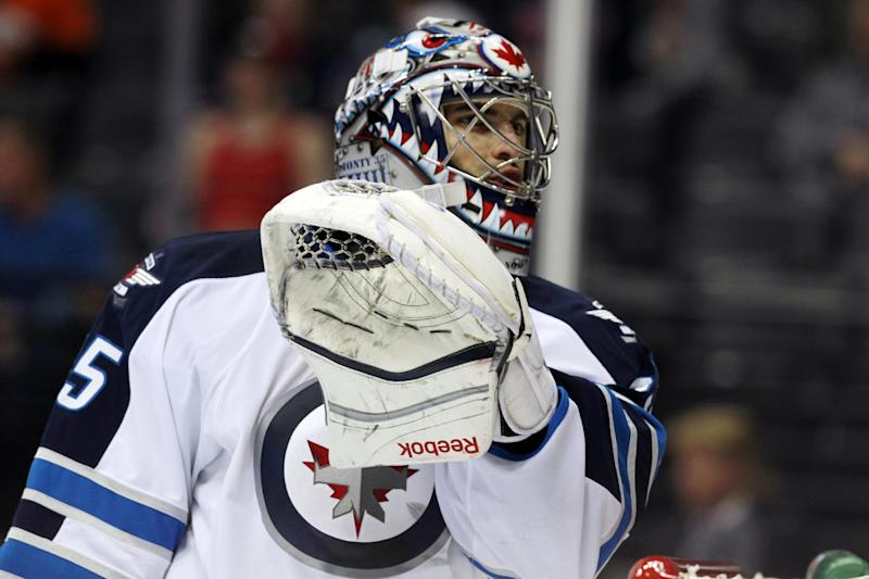 Winnipeg Jets goalie Al Montoya talks with a referee during a break in play against the Colorado Avalanche in the second period of an NHL hockey game in Denver on Sunday, Oct. 27, 2013. (AP Photo/David Zalubowski)