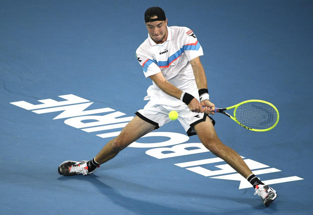Germany's Jan-Lennard Struff makes a backhand return to Serbia's Novak Djokovic during their first round singles match at the Australian Open tennis championship in Melbourne, Australia, Monday, Jan. 20, 2020. (AP Photo/Andy Brownbill)