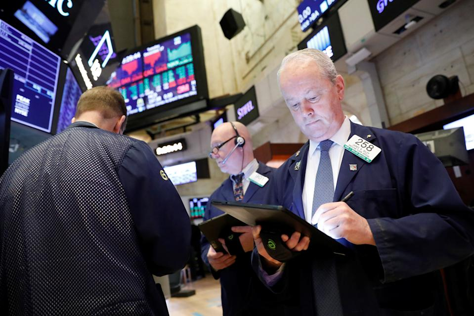 Traders work on the floor at the New York Stock Exchange (NYSE) in New York, U.S., December 17, 2019. REUTERS/Brendan McDermid