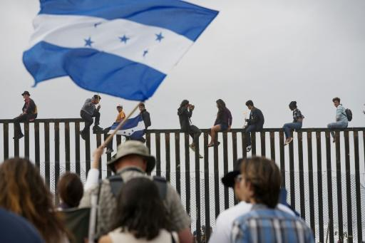 Migrant caravan demonstrators climb the US-Mexico border fence during a rally, on April 29, 2018, in San Ysidro, California