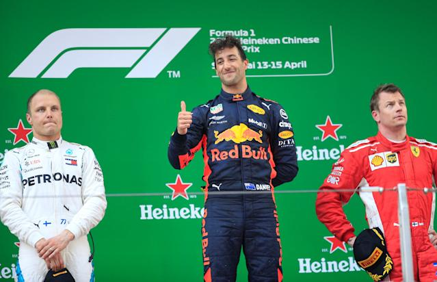 Formula One F1 - Chinese Grand Prix - Shanghai International Circuit, Shanghai, China - April 15, 2018 Red Bull's Daniel Ricciardo celebrates on the podium after winning the race as Mercedes' Valtteri Bottas and Ferrari's Kimi Raikkonen look on REUTERS/Aly Song