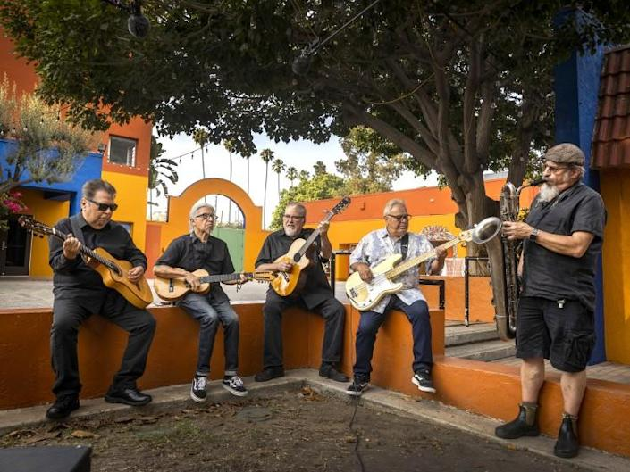 Los Angeles, CA - July 22: Los Lobos: left to right: Cesar Rosas, singer, songwriter and guitarist, Louie Perez, songwriter, percussionist and guitarist, David Hidalgo, singer-songwriter, accordion, violin, 6-string banjo, cello, requinto jarocho, percussion, drums and guitar, Conrad Lozano, bass, and Steve Berlin, saxophonist, keyboardist and record producer, are photographed at Plaza de la Raza on Thursday, July 22, 2021 in Los Angeles, CA. Archetypal LA band Los Lobos will release Native Sons, which features their version of classic L.A. songs including Sail On, Sailor (Beach Boys), The World Is A Ghetto (WAR) and Flat Top Joint (The Blasters). Now in their 40th year as a band, Los Lobos shoots a video for the National Endowment for the Arts at Plaza de la Raza in Lincoln Heights. (Allen J. Schaben / Los Angeles Times)