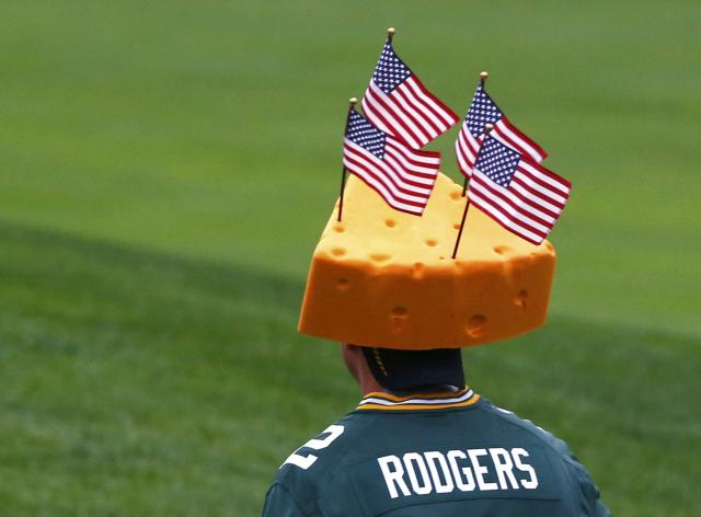 "A fan wears a ""cheesehead"" hat and Green Bay Packers Aaron Rodgers jersey during the continuation of the rain delayed Foursome matches for the 2013 Presidents Cup golf tournament at Muirfield Village Golf Club in Dublin, Ohio October 6, 2013. REUTERS/Jeff Haynes (UNITED STATES - Tags: SPORT GOLF)"