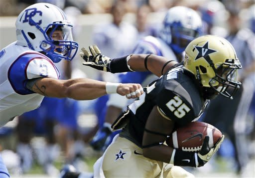 Presbyterian safety Brandon Leston (3) grabs the jersey of Vanderbilt running back Brian Kimbrow (25) in the first quarter of an NCAA college football game, Saturday, Sept. 15, 2012, in Nashville, Tenn. (AP Photo/Mark Humphrey)