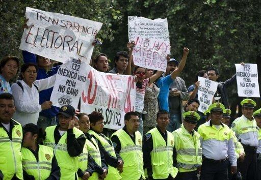 Demonstrators hold signs in front of the Federal Electoral Institute (IFE) in Mexico City. Mexico's national election authority on Wednesday announced a review of ballots at 54.5 percent of the polling stations in the country's weekend presidential election
