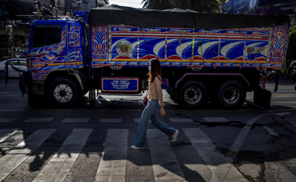 A woman, wearing a face mask, walks in the foreground of a truck in Bangkok, Thailand, Wednesday, May 13, 2020. Thai government continue to ease restrictions related to running business in capital Bangkok that were imposed weeks ago to combat the spread of COVID-19. (AP Photo/Gemunu Amarasinghe)