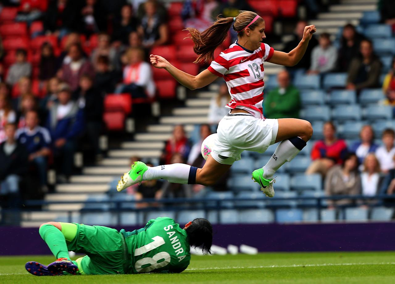GLASGOW, SCOTLAND - JULY 28: Alex Morgan of USA jumps over Sandra Sepulveda of Columbia during the Women's Football first round Group G match between United States and Colombia on Day 1 of the London 2012 Olympic Games at Hampden Park on July 28, 2012 in Glasgow, Scotland.  (Photo by Stanley Chou/Getty Images)