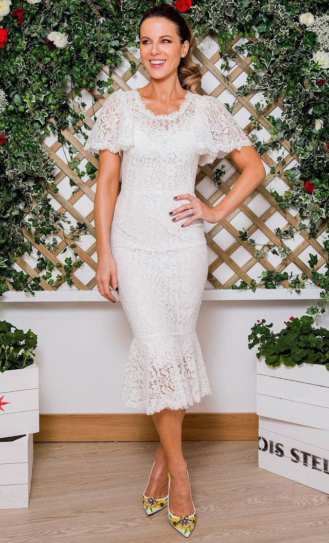 in a Dolce & Gabbana short-sleeve lace midi dress with a flounce hem paired with floral-print pumps at the Wimbledon Tennis Championships with Stella Artois in London.