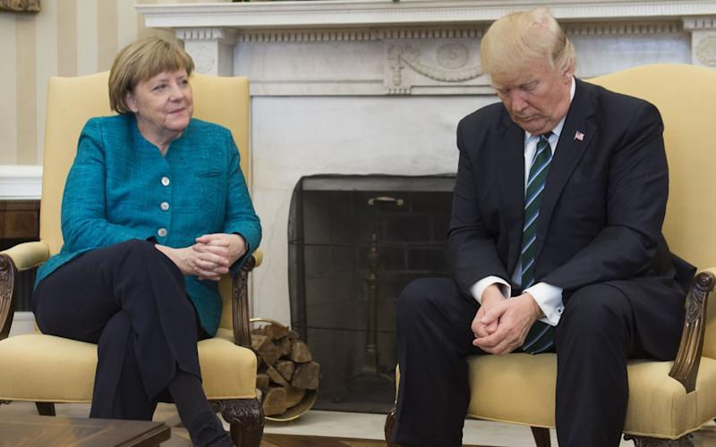 US President Donald Trump and German Chancellor Angela Merkel meet in the Oval Office of the White House in Washington - AFP or licensors