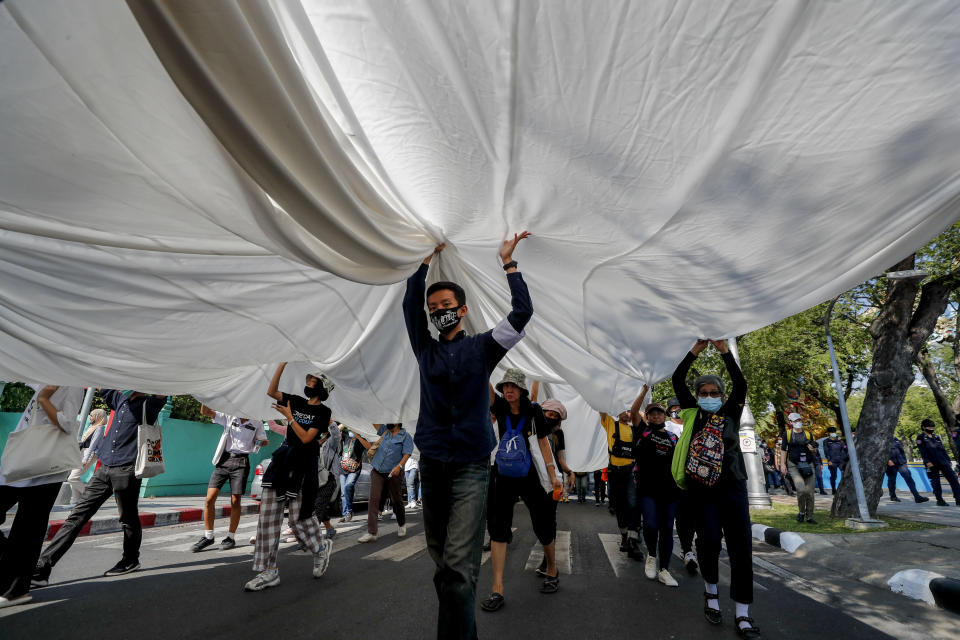 Students led pro-democracy protesters carry a massive white-fabric during a protest march to the Democracy Monument in Bangkok, Thailand, Saturday, Nov. 14, 2020. (AP Photo/Sakchai Lalit)