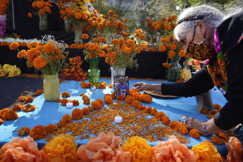 "Ofelia Esparza, 88, from East Los Angeles, arranges fresh marigolds, often called ""flowers of the dead,"" by a picture of late Los Angeles Lakers great Kobe Bryant left by members of the community, at an altar for Day of the Dead, titled ""2020 Memorial to Our Resilience,"" at Grand Park in Los Angeles, on Thursday, Oct. 29, 2020. (AP Photo/Damian Dovarganes)"