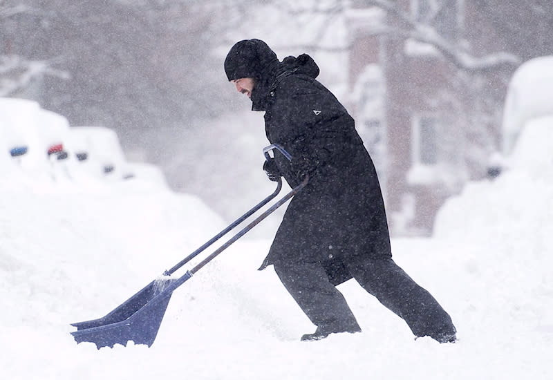 A man shovels snow during the winter season in Montreal. Photo from The Canadian Press.