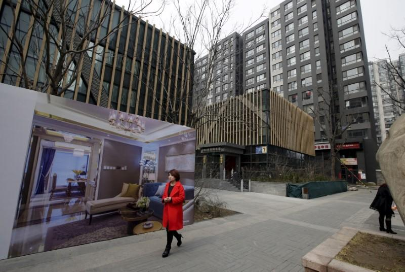 A man wowalks past a property poster outside luxury apartment blocks in central Beijing