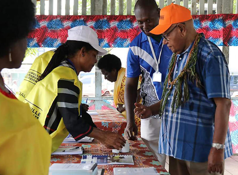 John Momis, right, president of the Autonomous Region of Bougainville, prepares to vote in Buka, Papua New Guinea, Saturday, Nov. 23, 2019, in a historic referendum to decide if they want to become the world's newest nation by gaining independence from Papua New Guinea. (Post Courier via AP)