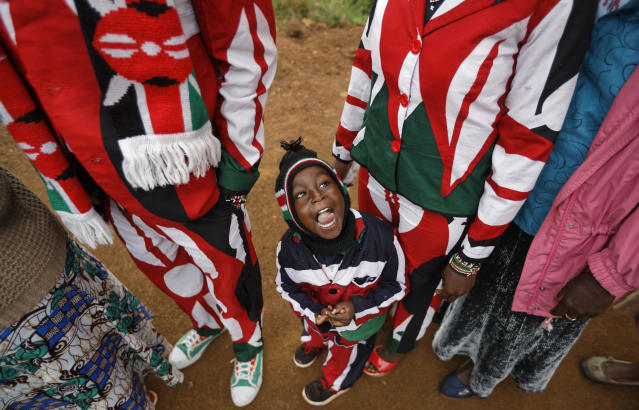 <p>Joseph Njoroge Kimani, 3, stands with his father James Kimani Njoroge, left, and mother Esther Wanjiru Njoroge, right, all wearing suits made in the colors of the Kenyan flag, as they queue to cast their votes in Gatundu, north of Nairobi, in Kenya Tuesday, Aug. 8, 2017. (Photo: Ben Curtis/AP) </p>
