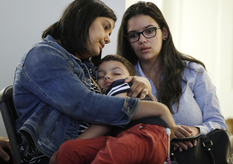 Sirlen Costa, of Brazil, holds her son Samuel, 5, as her niece Danyelle Sales, right, looks on during a news conference, Monday, Aug. 26, 2019, in Boston. Costa brought her son to the United States seeking treatment for his short bowel syndrome. Doctors and immigrant advocates say federal immigration authorities are unfairly ordering foreign born children granted deferred action for medical treatment to return to their countries. (AP Photo/Elise Amendola)