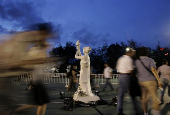 People walk past a statue of the Goddess of Democracy as they join a candlelight vigil at Hong Kong's Victoria Park June 4, 2007 to mark the 18th anniversary of the military crackdown of a pro-democracy movement at Beijing's Tiananmen Square in 1989.