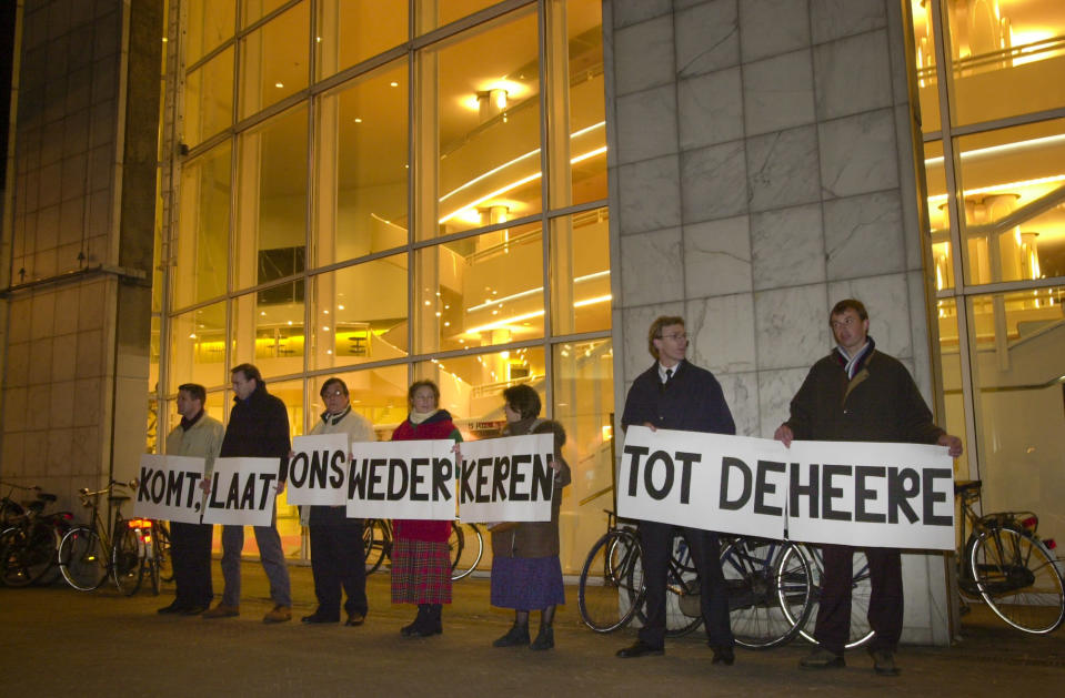 """Demonstrators stand outside Amsterdam's City Hall holding a biblical text from the Old Testament reading """"come let us return to the Lord"""" on April 1, 2001. Twenty years ago, the mayor of Amsterdam married four couples as the Netherlands became the first country in the world with legalized same-sex marriages. (AP Photo/Peter Dejong)"""