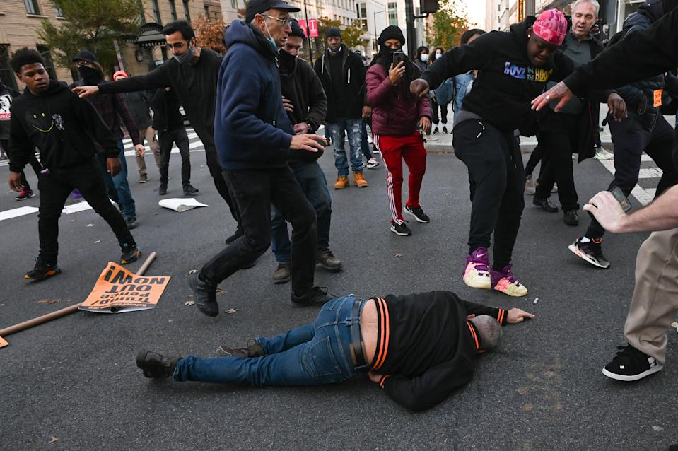 A supporter of US President Donald Trump lying on the floor is kicked as he is attacked by anti-Trump demonstrators in Washington, DC on November 14. Source: Getty