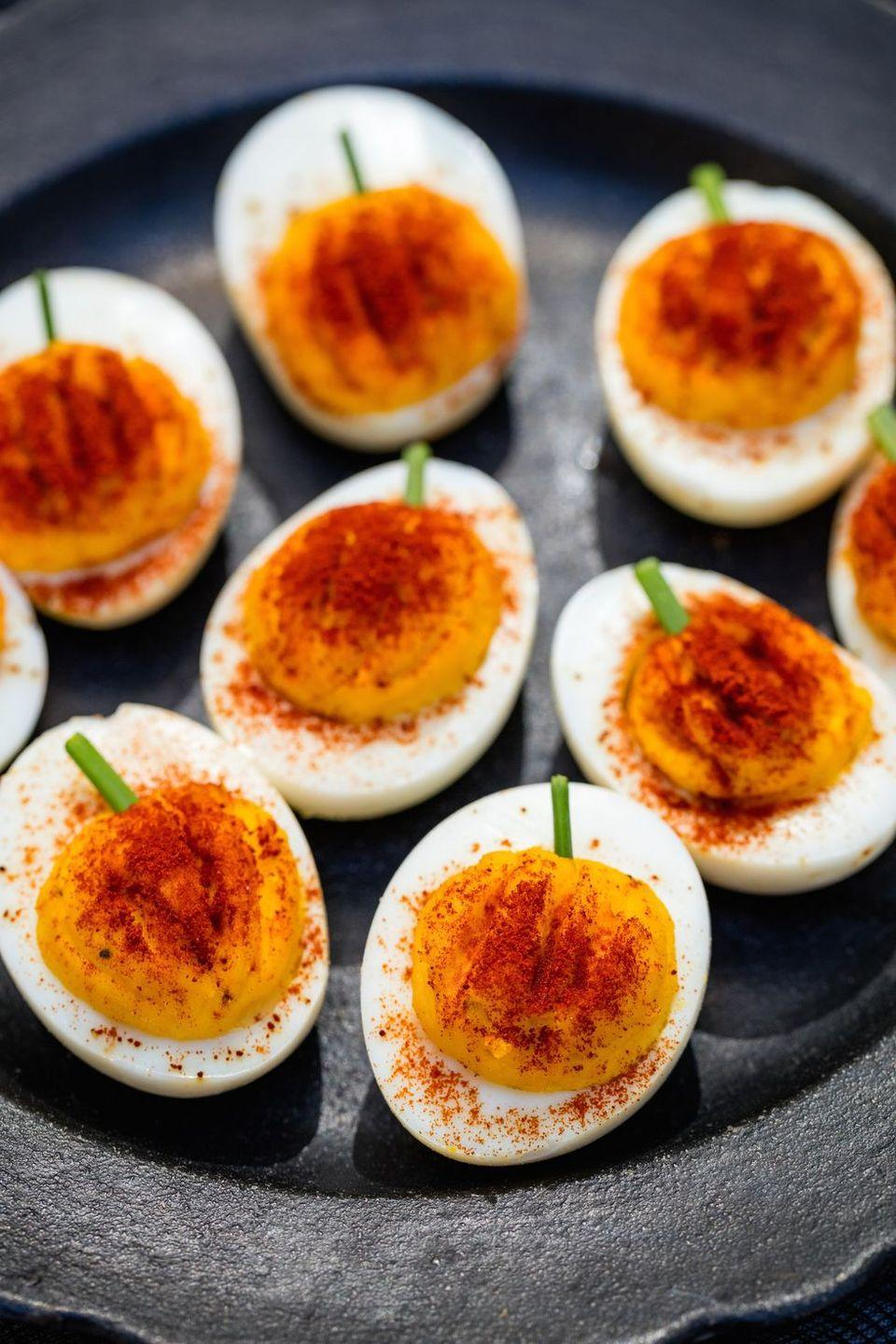 """<p>Deviled eggs are a perfect appetizer for a Halloween dinner. Spice them up with this fun pumpkin-influenced version. </p><p><strong><em>Get the recipe at <a href=""""https://www.delish.com/cooking/recipe-ideas/recipes/a44140/pumpkin-deviled-eggs-recipe/"""" rel=""""nofollow noopener"""" target=""""_blank"""" data-ylk=""""slk:Delish"""" class=""""link rapid-noclick-resp"""">Delish</a>. </em></strong></p>"""