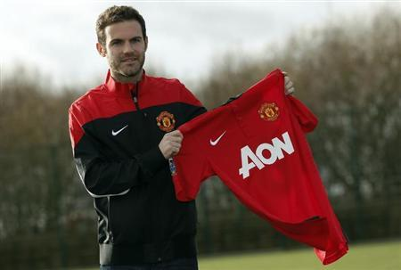 Manchester United's new signing Juan Mata holds a club shirt during a photocall at the club's Carrington training complex in Manchester, northern England, January 27, 2014. REUTERS/Phil Noble