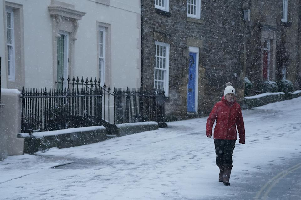 A woman walks through snow in Hexham, Northumberland. Heavy snow and freezing rain is set to batter the UK this week, with warnings issued over potential power cuts and travel delays. (Photo by Owen Humphreys/PA Images via Getty Images)