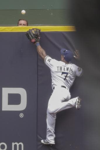 Milwaukee Brewers' Eric Thames can't catch a two-run home run hit by St. Louis Cardinals' Yadier Molina during the sixth inning of a baseball game Saturday, June 23, 2018, in Milwaukee. (AP Photo/Morry Gash)