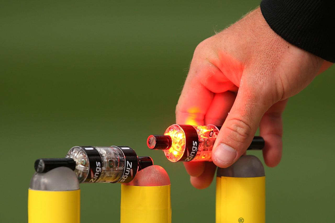 MELBOURNE, AUSTRALIA - DECEMBER 20:  A bail lights up after being lifted up by a Channel Ten staff member during the Big Bash League match between the Melbourne Stars and the Melbourne Renegades at Melbourne Cricket Ground on December 20, 2013 in Melbourne, Australia.  (Photo by Michael Dodge/Getty Images)